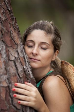 Young woman enjoying nature, embracing a tree trunk