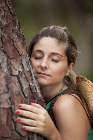 tree vertical: Young woman enjoying nature, embracing a tree trunk