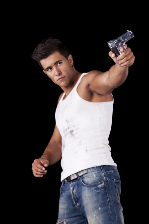 Powerful young man with a gun (isolated on black) photo