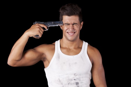 Stressed young man with a gun pointing to his head (isolated on black) photo