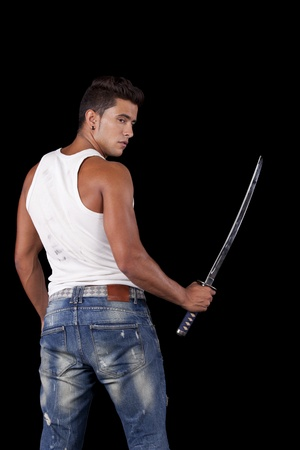 Young warrior holding a ninja sword (isolated on black) Stock Photo