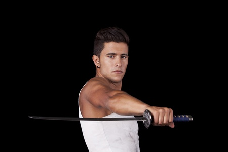 Young warr holding a ninja sword (isolated on black) Stock Photo - 11017318