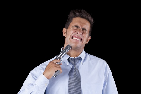 Stressed young businessman with a gun pointing to his head (isolated on black) Stock Photo - 11017604