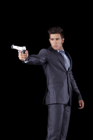Powerful businessman with a gun (isolated on black) Stock Photo - 11017537