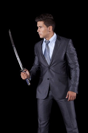 swords: Powerful businessman holding a ninja sword (isolated on white) Stock Photo