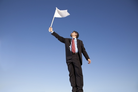 businessman asking for surrendering holding a white flag photo