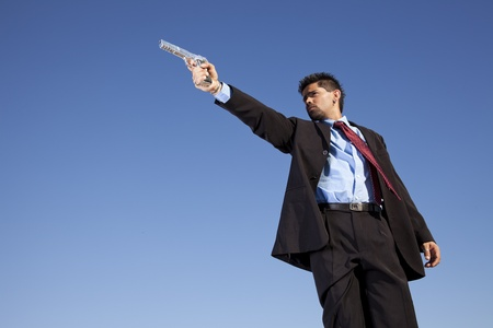 Powerful businessman with a gun in outdoor photo