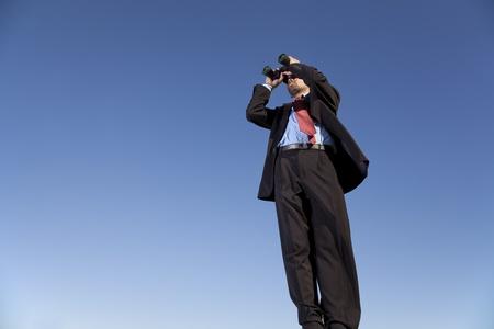 binoculars view: Businessman looking through his binoculars in outdoor