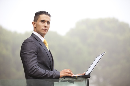 Confident young businessman working with his laptop at the office balcony photo