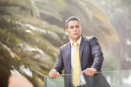 Confident young businessman at his office balcony (with backlight) photo