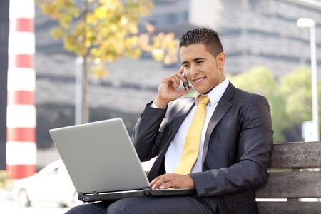 Businessman working sited in a bench at the city park photo