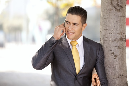 Successful and handsome businessman talking at his cellphone next to a tree photo