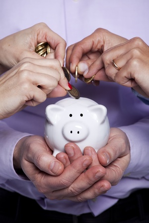 Group of business people saving money on the piggy bank photo
