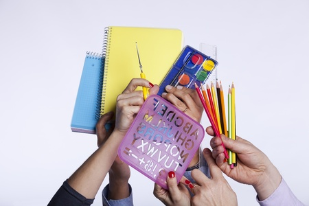 Group of hands holding education objects (selective focus) photo