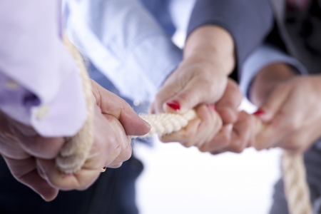 Group of woman hands pulling a rope competing with a man (selective focus) Standard-Bild
