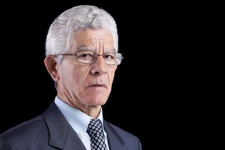 Senior businessman looking to you (isolated on black) Standard-Bild