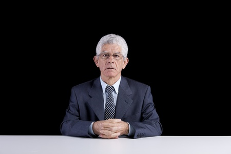 Senior businessman waiting at his desk  (isolated on black) photo