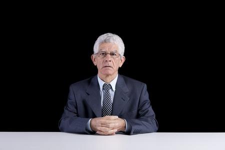 Senior businessman waiting at his desk  (isolated on black)