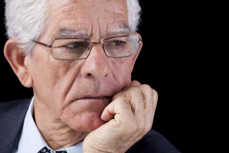 hombre preocupado: El pensamiento de negocios superior con la mano en la barbilla (aislado en negro)