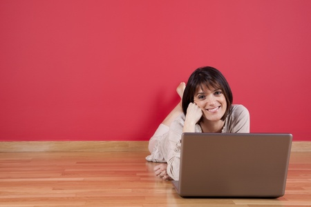 Woman using the laptop computer at her house floor, next to a red wall (selective focus) Stock Photo - 11017613