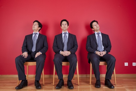 three confident businessman relaxing in a chair, next to a red wall photo