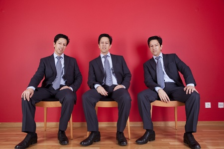 three confident businessman relaxing in a chair, next to a red wall Stock Photo - 11017767