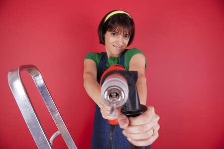 Happy woman holding an electric drill photo