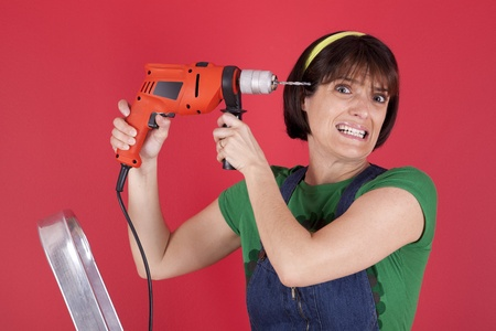 electric drill: Woman making a hole on her head with a electric drill Stock Photo