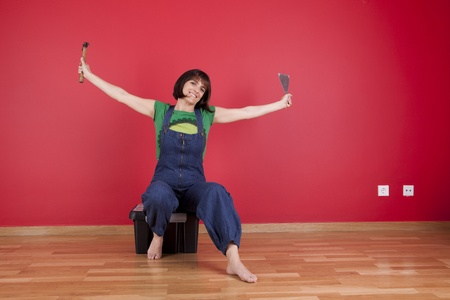 arms  outstretched: woman relaxing at her house after reparing her red wall Stock Photo
