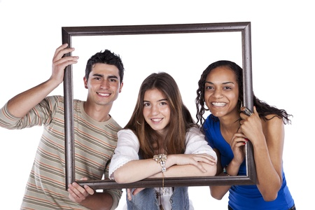 Three happy teenager friends inside a picture frame (isolated on white) Stock Photo
