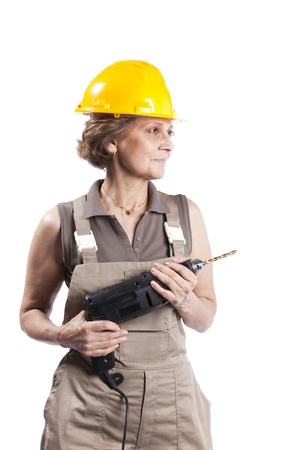 electric drill: Happy senior woman holding a drill tool (isolated on white)