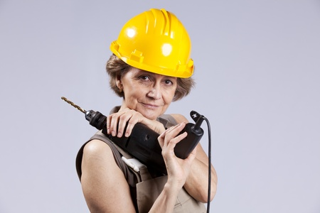 Happy senior woman holding a drill tool (isolated on gray) photo