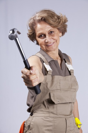 Senior woman with a hammer (gray background) photo