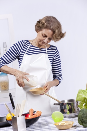 Beautiful and happy senior woman cooking at her kitchen photo
