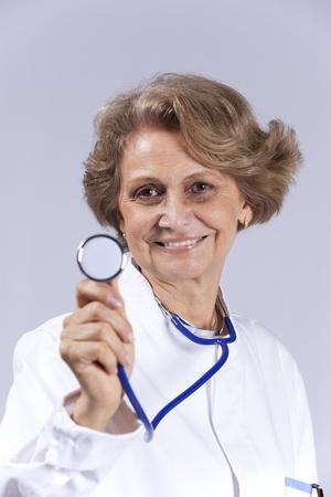 Happy senior doctor smiling (isolated on gray) photo