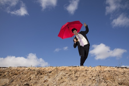 Businessman holding an umbrella at the edge of a cliff photo