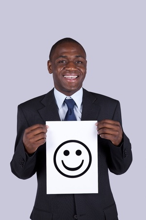 impostor: african businessman holding a happy face symbol printed on a paper