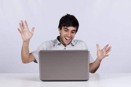 cara sorprendida: joven, sorprendido y feliz con algo que ver en su ordenador portátil