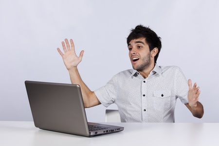 young man surprised and happy with something he see on his laptop photo