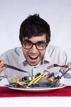 Crazy young man eating technology at his dinner plate photo