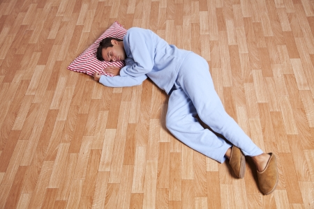 Young man dress with nightclothes sleeping on the floor (isolated on white) Stock Photo - 16466226