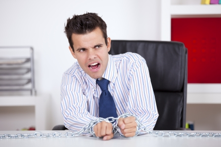 Businessman slave trapped with chains at his own office Stock Photo - 16384315