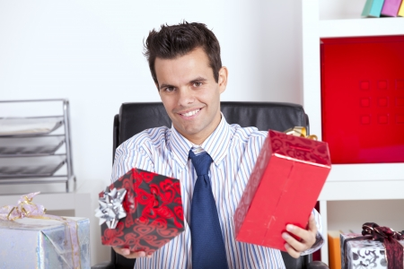 Happy businessman at his office giving christmas gifts Stock Photo - 16384522