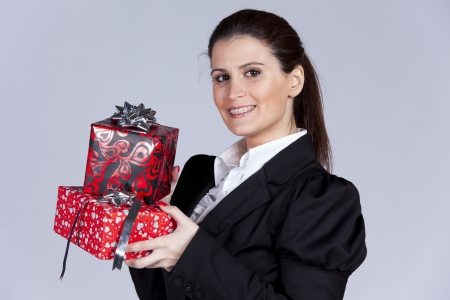 Businesswoman with a lot of gift packages (isolated on gray) photo