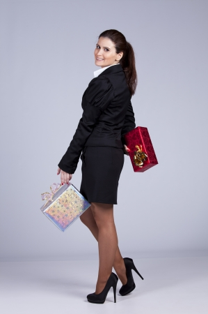 Businesswoman with a lot of gift packages (isolated on gray) Stock Photo - 16466199