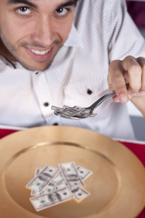 Man eating money at a plate with a fork and a knife photo