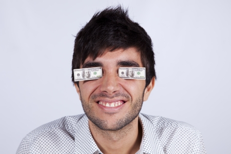 Young man with little dollar bills covering his eyes Stock Photo - 16466213