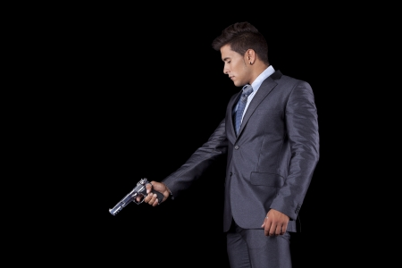 Powerful businessman with a gun (isolated on black) Stock Photo - 16386625