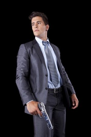 gun shot: Powerful businessman with a gun (isolated on black)