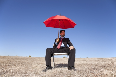Businessman sited on a chair in a landscape holding a red umbrella